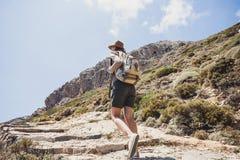 Ragazza del viaggiatore che cammina con lo zaino in montagne immagini stock