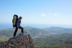 Ragazza del viaggiatore con zaino e sacco a pelo che si leva in piedi su un'alta roccia Fotografia Stock Libera da Diritti