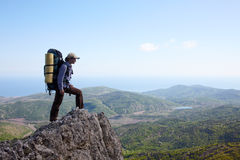 Ragazza del viaggiatore con zaino e sacco a pelo che si leva in piedi su un'alta scogliera Fotografia Stock Libera da Diritti