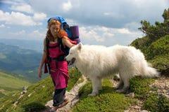 Ragazza del viaggiatore con zaino e sacco a pelo con il cane Immagini Stock Libere da Diritti