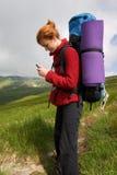 Ragazza del viaggiatore con zaino e sacco a pelo con il telefono Fotografia Stock