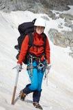 Ragazza del viaggiatore con zaino e sacco a pelo con l'ghiaccio-ascia Immagine Stock