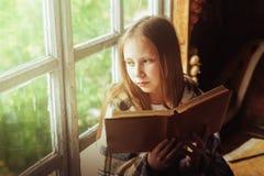 Ragazza del villaggio con un libro dalla finestra Fotografia Stock Libera da Diritti