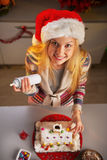 Ragazza dell'adolescente che decora la casa del biscotto di natale Fotografie Stock