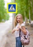 Ragazza dell'adolescente che mostra i pollici su contro il passaggio pedonale Fotografia Stock