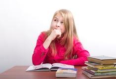 Ragazza dell'adolescente che si siede ad una tavola davanti lei Immagini Stock