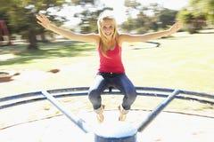 Ragazza dell'adolescente che si siede sulla rotonda del campo da giuoco immagini stock libere da diritti