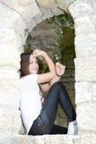Ragazza dell'adolescente che si siede sulle vecchie finestre antiche Immagine Stock