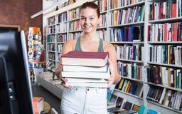 Ragazza dell'adolescente che tiene una pila di libri in una libreria Immagine Stock