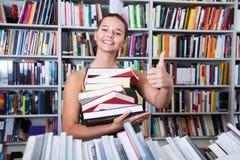 Ragazza dell'adolescente che tiene una pila di libri in una libreria Fotografie Stock