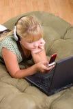Ragazza dell'adolescente con il telefono delle cellule e del computer portatile Fotografia Stock