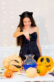 Ragazza dell'adolescente in costume del gatto che posa con le zucche Fotografie Stock