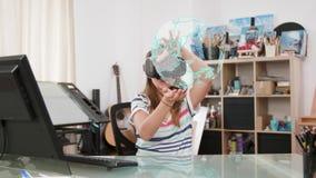 Ragazza dell'adolescente nella sua aula magna che impara circa il pianeta con la cuffia avricolare di realtà virtuale di VR video d archivio