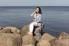 Ragazza dell'adolescente sulle rocce dal mare immagine stock