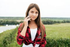 Ragazza dell'adolescente in una camicia rossa, di estate nelle chiamate della natura sul telefono fotografia stock libera da diritti