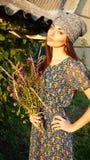 Ragazza dell'agricoltore con i fiori selvaggi in un villaggio Fotografie Stock