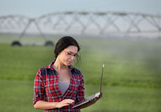 Ragazza dell'agricoltore con il computer portatile davanti all'impianto di irrigazione sul campo Immagine Stock