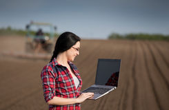 Ragazza dell'agricoltore con il computer portatile nel campo Fotografia Stock Libera da Diritti