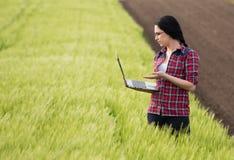 Ragazza dell'agricoltore con il computer portatile nel campo Immagine Stock Libera da Diritti