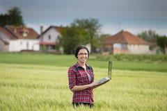 Ragazza dell'agricoltore con il computer portatile nel campo Immagine Stock