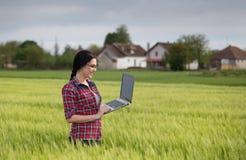 Ragazza dell'agricoltore con il computer portatile nel campo Fotografie Stock Libere da Diritti