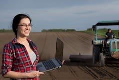 Ragazza dell'agricoltore con il computer portatile nel campo con il trattore Immagini Stock Libere da Diritti