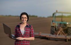 Ragazza dell'agricoltore con il computer portatile nel campo con il trattore Fotografia Stock