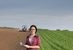 Ragazza dell'agricoltore con il computer portatile nel campo con il trattore Fotografia Stock Libera da Diritti