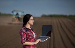 Ragazza dell'agricoltore con il computer portatile nel campo con il trattore Fotografie Stock