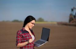 Ragazza dell'agricoltore con il computer portatile nel campo con il trattore Immagine Stock