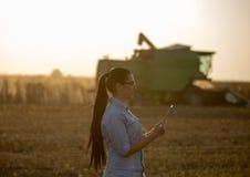 Ragazza dell'agricoltore con la compressa e la mietitrebbiatrice Fotografia Stock Libera da Diritti