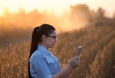 Ragazza dell'agricoltore con la compressa e la mietitrebbiatrice Fotografie Stock