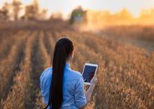 Ragazza dell'agricoltore con la compressa e la mietitrebbiatrice Fotografia Stock