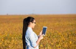 Ragazza dell'agricoltore con la compressa nel giacimento della soia Fotografia Stock Libera da Diritti