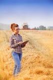 ragazza dell'agricoltore della Rosso-testa che spiega il raccolto nel giacimento di grano Fotografie Stock Libere da Diritti