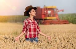 Ragazza dell'agricoltore e mietitrebbiatrice nel giacimento di grano Fotografie Stock Libere da Diritti