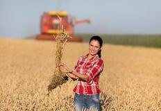 Ragazza dell'agricoltore e mietitrebbiatrice nel giacimento di grano Immagine Stock