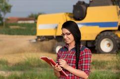 Ragazza dell'agricoltore sul campo con la mietitrebbiatrice Immagini Stock Libere da Diritti