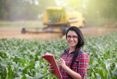 Ragazza dell'agricoltore sul campo con la mietitrebbiatrice Fotografie Stock