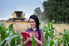 Ragazza dell'agricoltore sul campo con la mietitrebbiatrice Fotografia Stock Libera da Diritti
