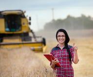 Ragazza dell'agricoltore sul campo con la mietitrebbiatrice Fotografia Stock