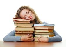 Ragazza dell'allievo che dorme abbracciando i libri Fotografie Stock Libere da Diritti