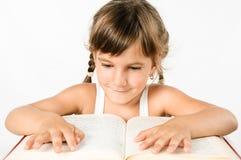 Ragazza dell'allievo che legge un grande libro isolato sul bianco Immagini Stock