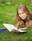 Ragazza dell'allievo che legge un libro in sosta Immagini Stock