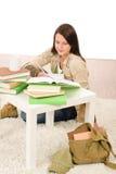 Ragazza dell'allievo che studia a casa seduta sul pavimento Immagine Stock