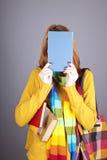 Ragazza dell'allievo con il libro blu vicino alla testa. Immagine Stock