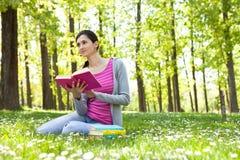Ragazza dell'allievo con il libro su erba Fotografie Stock