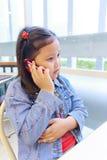 Ragazza dell'Asia che per mezzo del telefono Fotografie Stock Libere da Diritti
