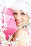 Ragazza dell'assistente della Santa con il contenitore ed il fiocco di neve di regalo dentellare Fotografia Stock