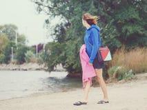 Ragazza della donna sulla spiaggia il giorno freddo ventoso Fotografia Stock